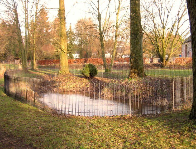 La clôture métallique de 115 cm de haut entoure un étang.