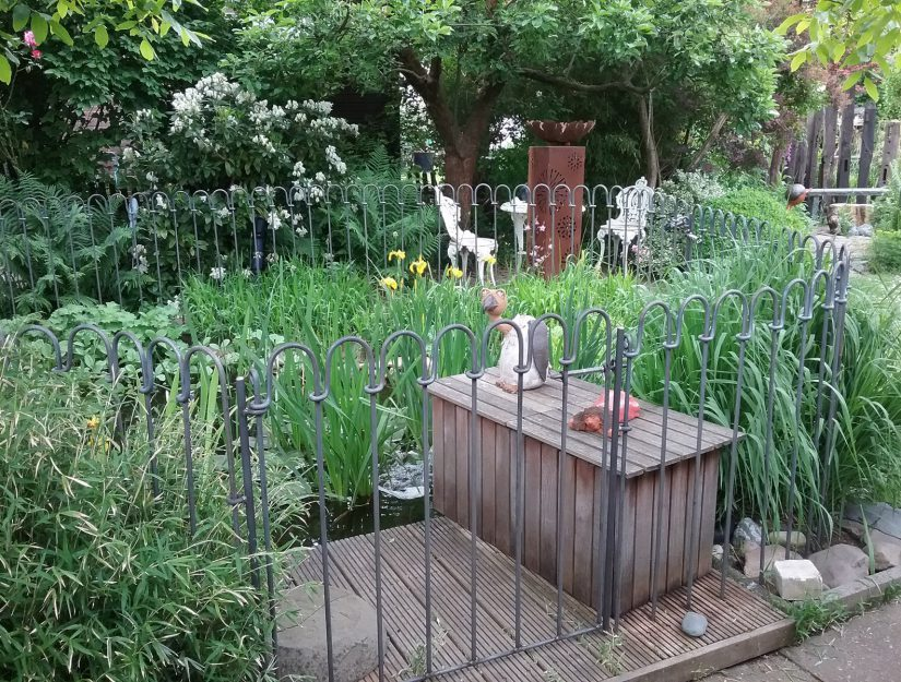 Teichzaun Tür auf einem Holzdeck vor einem Gartenteich.
