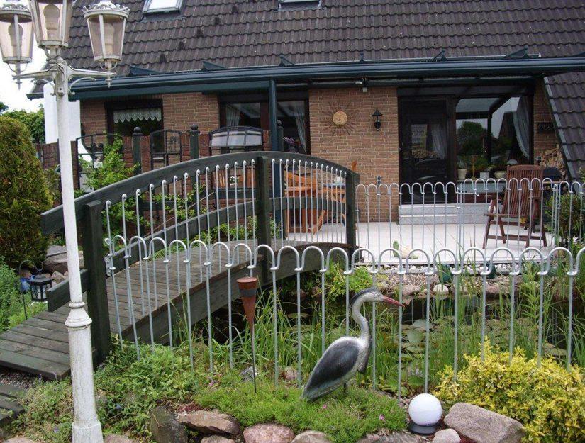 Eine Gartenbrücke aus Holz mit Endstäbe als Geländerstäbe.