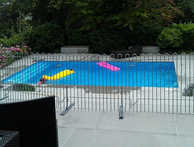 La grille rabbit galvanisée sur pieds devant une piscine comme dispositif de sécurité pour les enfants.