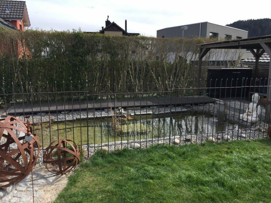Gesteckter Zaun aus Eisen vor einem Gartenteich in der Schweiz