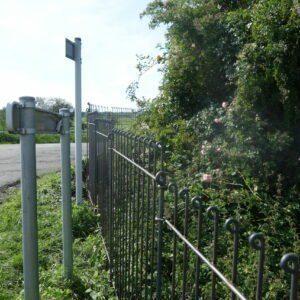 Zaun aus Metall zwischen der Straße und der Grundstückseinfassung