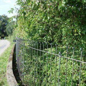 Zaun aus Stahl hinter einer Betonmauer