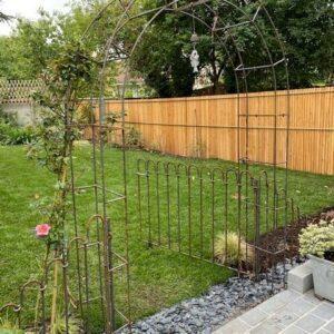 Jardin avec un arc et un rosier à côté de la porte