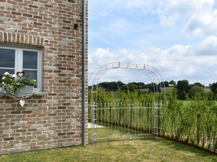 Der Durchgang zwischen Haus und Hecke wird mit einem Rosenbogen mit Tor versperrt