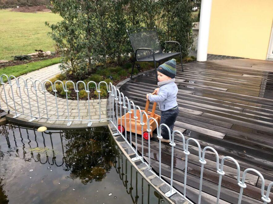 Das Kind kann wegen dem Zaun nicht in das Wasserbecken fallen