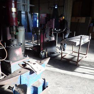 In der gegenüberliegenden Halle schmiedet Christophe Erdspitzen für den Teichzaun mit dem Lufthammer.