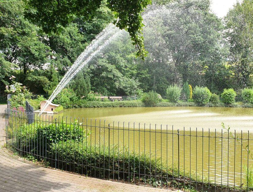 Zaun an einem See in einem Park neben einem Altersheim.