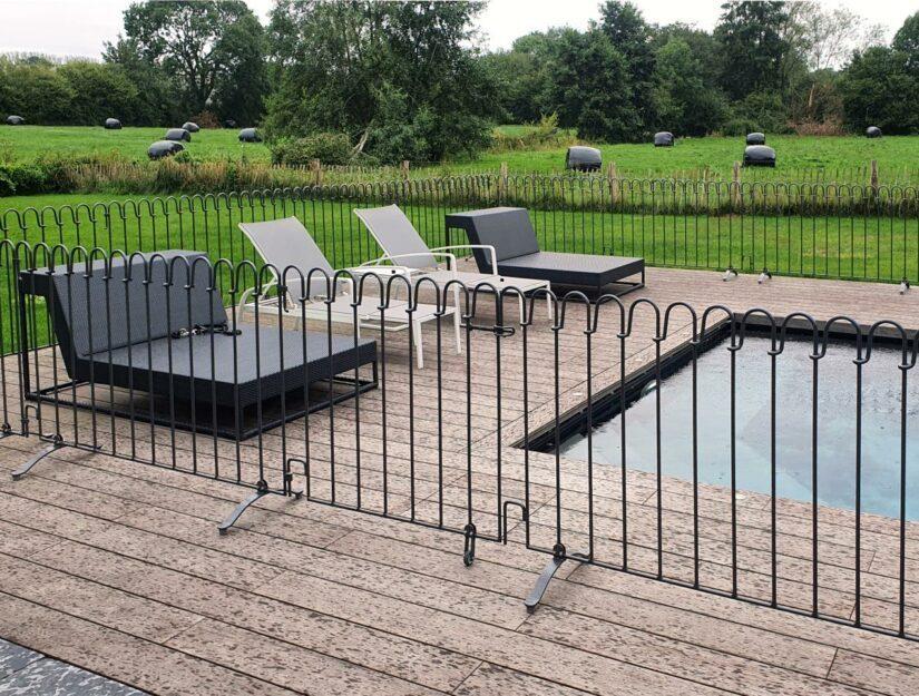 La clôture de la piscine avec la porte a été peinte en noir par le client.