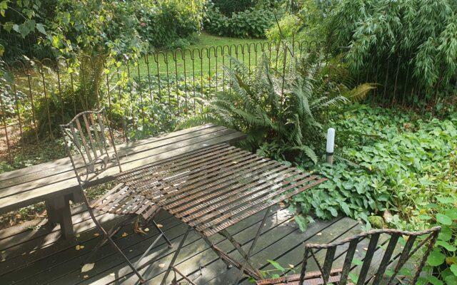 Eingezäunter Gartenteich mit Sitzecke