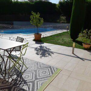 La clôture de la piscine est simplement posée sur les dalles de la terrasse avec les pieds en caoutchouc