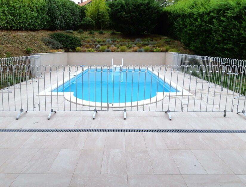 Poolzaun aus verzinktem Stahl vor einem privaten Schwimmbecken.