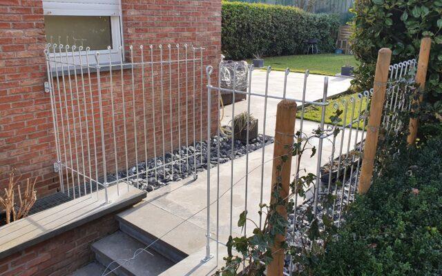 Zaun zwischen Haus und Hecke über eine Treppe