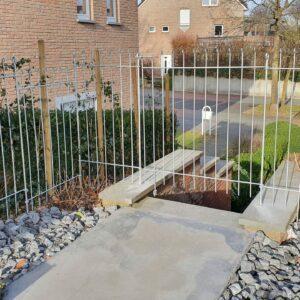 Zaun über die Treppe zwischen Hecke und Haus
