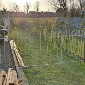 Verzinkter Steckzaun mit einer Gartentür zwischen Haus und Hecke