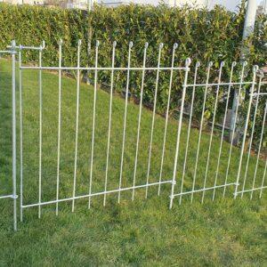 Verzinkter Zaun mit einer Gartentür zwischen Haus und Hecke