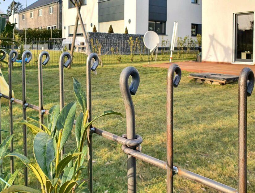 Grundstücksumzäunung aus Stahl vor einer Kirschlorbeer-Hecke.