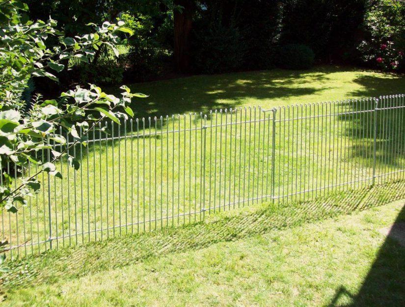 Der verzinkte Metallzaun dient als Abtrennung für einen Garten.