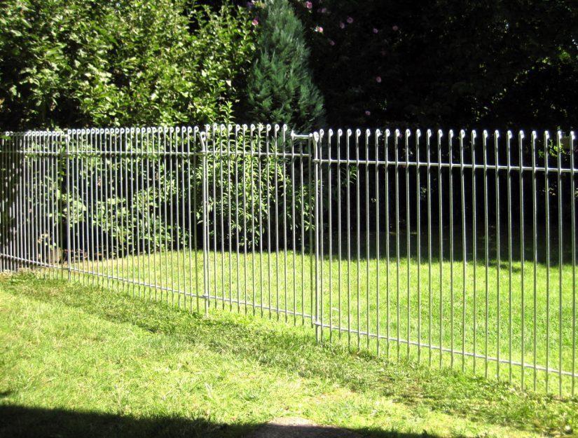 Stabiler Zaun aus verzinktem Eisen mit einer Tür als Durchgang.