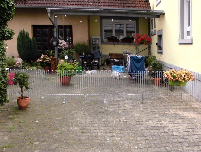 Der Zaun mit den Standfüßen trennt den Hof für die Katze ab.