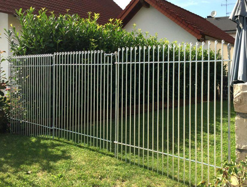 Clôture de jardin entre la maison et la haie équipée d'une porte galvanisée.
