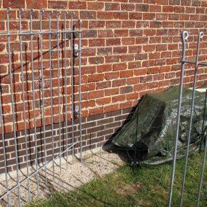 La porte de la clôture est attachée au mur avec des fixation murales