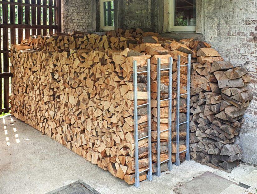 La pile de bois ne bascule plus. Le bois de chauffage est empilé contre le support.