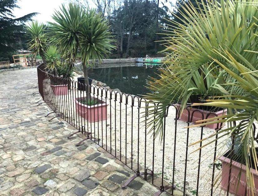 Der braun lackierter Zaun steht auf Pflastersteinen vor einem See.