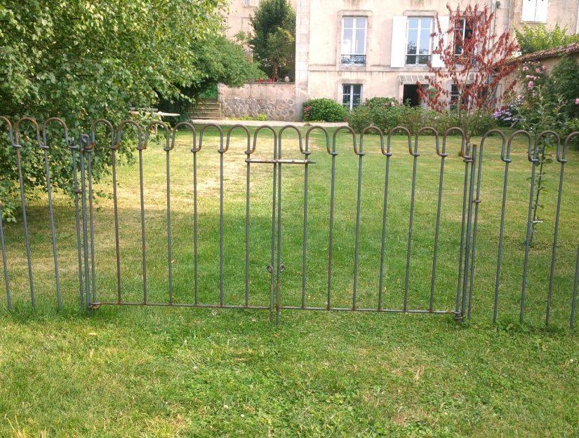Das doppelflügelige Tor aus Metall teilt den Garten in zwei Bereiche.
