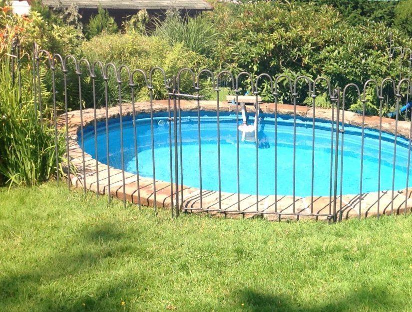 Clôture avec portail devant une piscine dans le jardin.