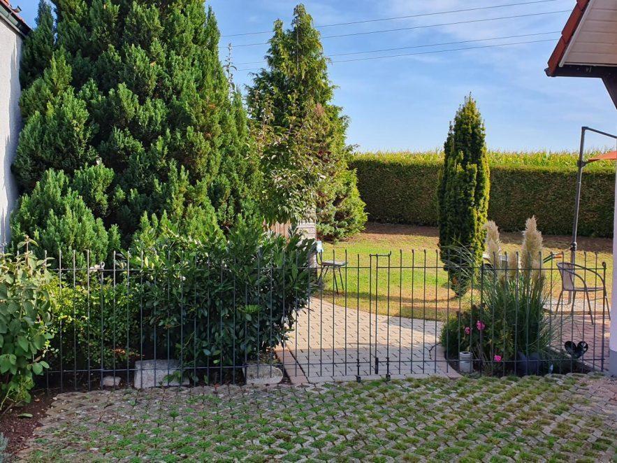 Gartenzaun aus Eisen mit großem Doppeltor in der Mitte.