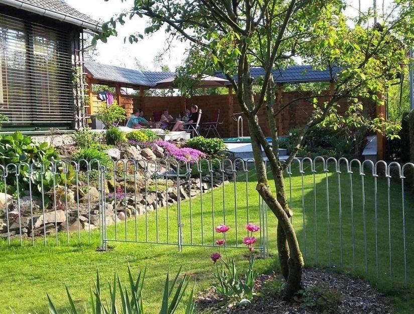 La grande porte palvanisée divise le jardin en deux parties.