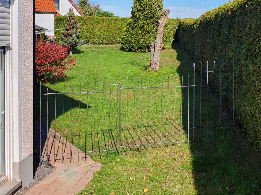 Gartenzaun aus Metall vom Haus bis zur Nachbar-Hecke mit einem Tor