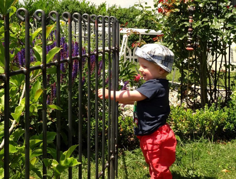 Das Kind kann nicht an den Teich gelangen. In der rohen Ausführung wird dieser Zaun schnell Rost ansetzen.
