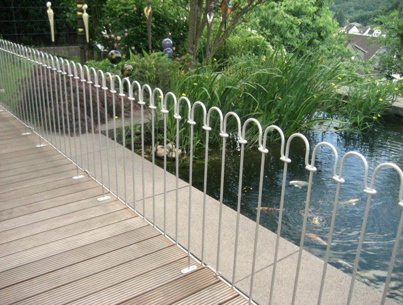 Verzinkter Zaun in einer Linie auf einer Terrasse aufgeschraubt.