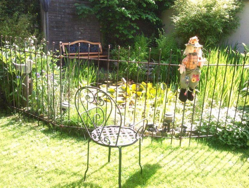 Gemütliche Gartenecke neben dem Zaun am Teich.