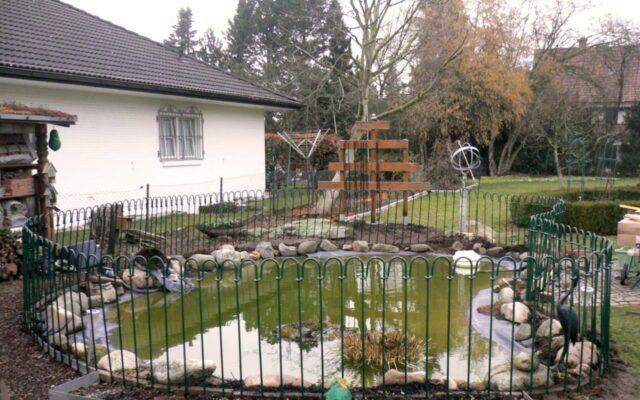 Clôture en métal peint vert placée autour de l'étang
