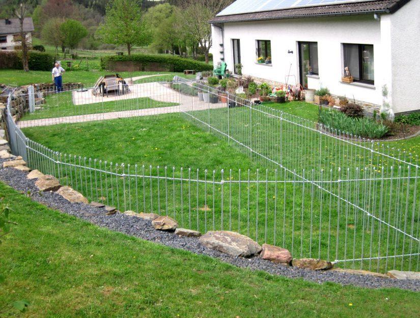 Hundeauslauf (Gehege) auf dem Rasen an einer Mauer.