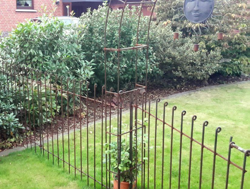 Im Zaun integrierter Rosenbogen mit Tor roh (darf rosten).