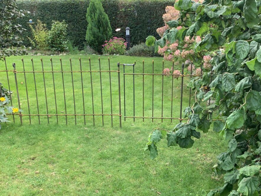 Niedrige Gartenabtrennung mit dem rostigen Eisenzaun und der Tür