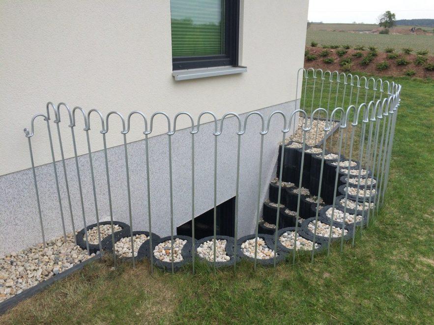 Steckzaun im Rasen vor einem Kellerloch mit Fenster