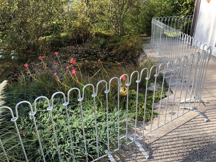 Der Zaun der auf Füßen steht verhindert, dass die Kinder in den Teich fallen.