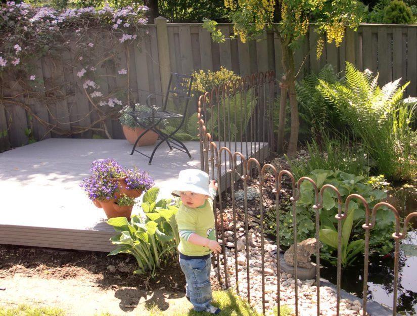 Clôture sécurisée pour les enfants entre un étang de jardin et un coin détente.