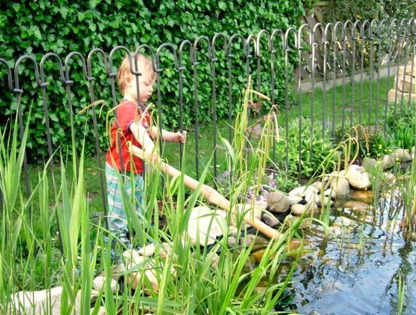 Der kleine Junge kann wegen dem Teichzaun nicht ins Wasser fallen.