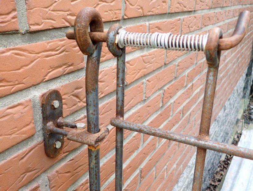 Der Wandhalter mit Klemmführung in roh (darf rosten) hält den Verbindungsstab für den Türriegel.