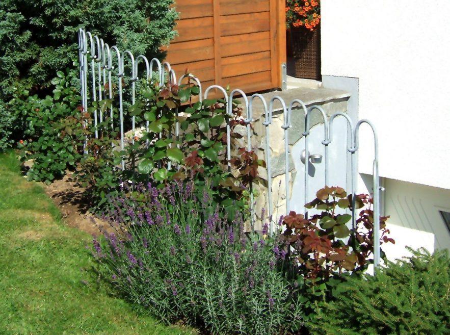 Metall Zaun vor einem Kellerloch auf dem Rasen