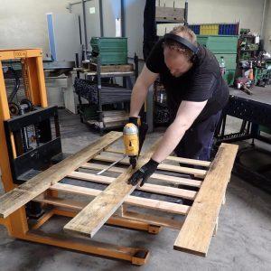Eine Palette wird für den Zaun vorbereitet und bekommt Bretter aufgenagelt