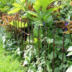 Die Zäune trennen die Blumenbeete sauber vom Rasen ab.