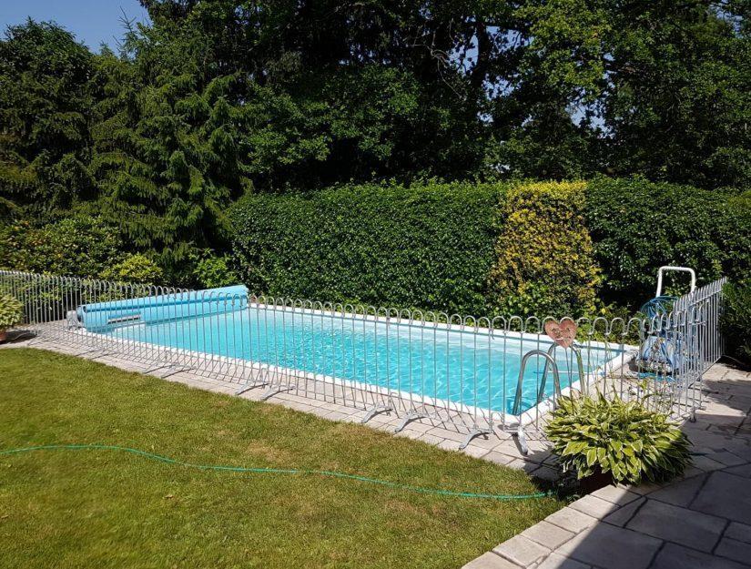 Der Pool im Garten ist mit einem kindersicheren Stell-Zaun gesichert.