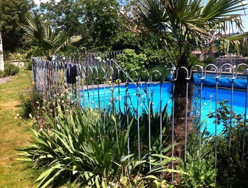 Kindersicherer verzinkter Steckzaun vor einem Pool in Südeuropa.
